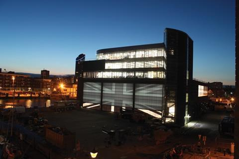 The site's stacked form at night