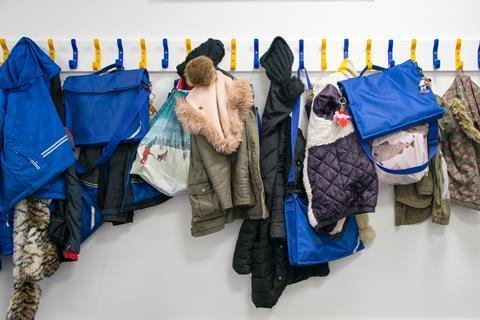 Children's coats and school bags hung on pegs