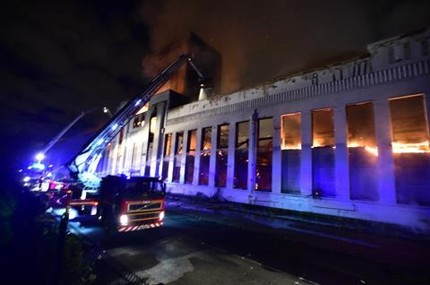 Firefighters douse the burning Littlewoods Building in Liverpool