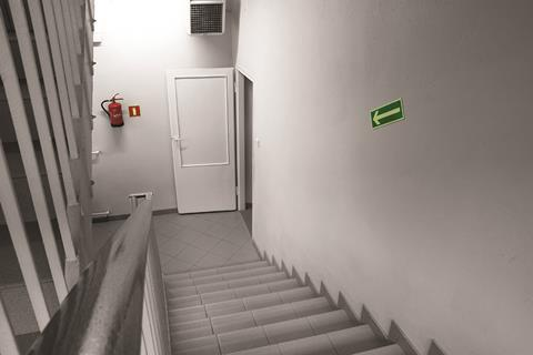 A clearly signposted open door at the bottom of a flight of stairs with a fire extinguisher next to it