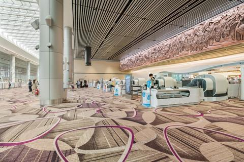 View of security at Changi airport terminal 4 which was designed by Benoy. An immersive media wall by Moment Factory is visible on the right